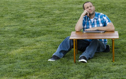 Dreaming of the future to come. Man sitting and looking out at a table outside on the grass wearing a plaid shirt with a laptop computer on the picnic table Royalty Free Stock Photos
