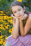 Dreaming in the garden. A young girl sits in the garden dreaming stock photo