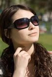Dreaming Girl. Young woman in bright sunshine wearing black sunglasses, long dark hair, dreaming or daydreaming Royalty Free Stock Images
