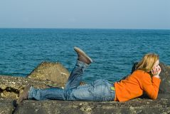 Dreaming girl. Laying on the rock at seaside Royalty Free Stock Photo