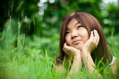 Dreaming girl. Summer. Portrait of pretty asiatic girl dreaming at meadow Stock Image