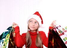 Dreaming girl as Mrs. Santa with shopping bags Stock Photo