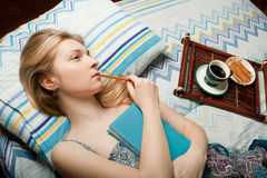 Dreaming girl with cup of tea and notebook Royalty Free Stock Photo