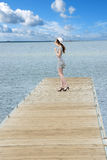Dreaming girl in elegat dress on lakes pier Stock Photography