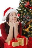 Dreaming girl with gifts sitting under Christmas tree. Dreaming Santa girl with gifts sitting under Christmas tree Royalty Free Stock Images