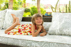 Dreaming girl. The little girl dreams of lying on the couch Royalty Free Stock Photo