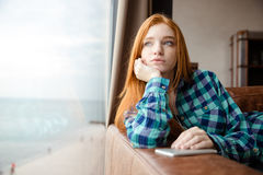 Dreaming girl looking out of window and listening to music Royalty Free Stock Images