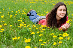 Dreaming girl lying among dandelions Stock Photo