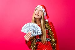 Dreaming girl in a red sweater and a hat of Santa Claus, makes p stock images
