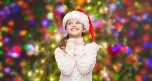 Dreaming girl in santa helper hat Stock Images