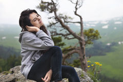 Dreaming girl sits on the edge of the cliff Stock Photos
