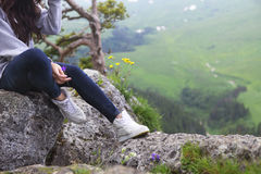 Dreaming girl sits on the edge of the cliff Stock Images