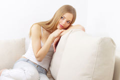 Dreaming girl sitting on sofa Royalty Free Stock Photos
