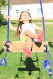 Dreaming girl on swing Royalty Free Stock Photo