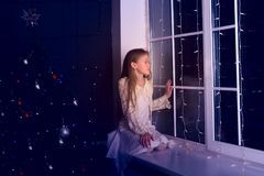 Dreaming girl teenager sits on a window sill Royalty Free Stock Image