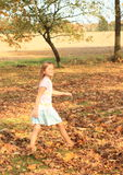 Dreaming girl walking barefoot in dead leaves Stock Image