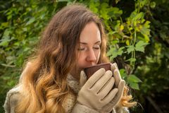 Dreaming girl in warm clothes on autumn park testing a hot bever stock photos