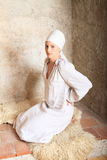 Dreaming girl. Young woman - dreaming girl in white dress and headscarf kneeing on fur Royalty Free Stock Images