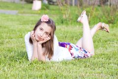 Dreaming girls rest on the green grass Stock Images