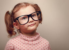 Dreaming happy kid girl in glasses. Closeup Royalty Free Stock Photos