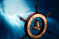 Dreaming Of The High Seas 1. Still-life of a model steering will and a bell against textured background of stormy sea and rays of sunlight. Color photography Stock Photo