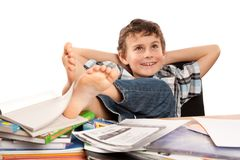 Dreaming of holiday. Portrait of a barefoot schoolboy with his feet up on his desk, waiting for holiday to come Royalty Free Stock Photos