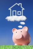 Dreaming a home. A pink piggy bank with new home house imagination vision in the air with blue sky Royalty Free Stock Photography