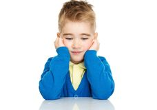 Dreaming little boy in blue cardigan. And yellow shirt Stock Photos