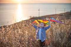 Dreaming little boy holding kite above head among a field of golden spikes against the sea coast at sunset. Beautiful little boy wearing shirt and T-shirt stock photo