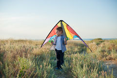 Dreaming little boy holding a kite behind his shoulders. Dreaming little boy with eyes closed holding a kite behind his shoulders Royalty Free Stock Photos