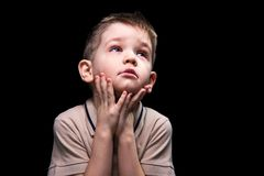 Dreaming little boy. Photo of little boy on black background Stock Photo