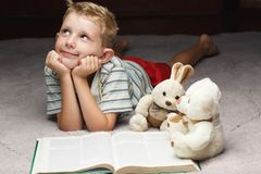 Dreaming little boy reading book with his favorite toys. On a soft plush blanket Stock Images