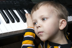 Dreaming little boy sitting at the piano Stock Photos