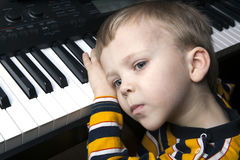 Dreaming little boy sitting at the piano. Portrait of a dreaming little boy sitting at the piano Stock Image