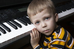Dreaming little boy sitting at the piano Royalty Free Stock Images