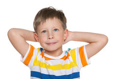 Dreaming little boy on the white. A dreaming little boy in striped shirt on the white background Royalty Free Stock Images