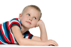 Dreaming little boy on the white. A dreaming little boy in striped shirt on the white background Stock Photography
