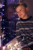 Dreaming little boy on the windowsill with Christmas Lites Royalty Free Stock Photo