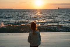 Dreaming little girl looking at the sea storm and sunset in autumn. Dreaming little girl with hair lit by warm sunlight looking at the sea sunset in autumn Stock Photography