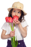 Dreaming little girl with red tulips Royalty Free Stock Image