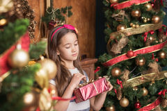 Dreaming little girl wearing red headband opens gift near christmas tree. stock images