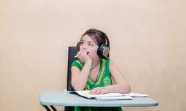 Dreaming little pretty girl sitting behind a table and looking away with a headphones on her head Royalty Free Stock Images