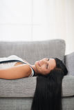 Dreaming long hair young woman laying on couch Royalty Free Stock Photos