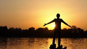 Dreaming man keeps hands aside on a lake bank at sunset. An amazing view of a young man who stands on tree roots and keeps his hands aside on a forest lake bank stock video footage