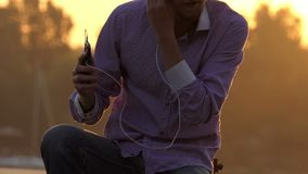 Dreaming man sits on a lake bank with golden sun path in slo-mo. An optimistic closeup of a young blond man who listens to the music on his mobile and sits on a stock footage