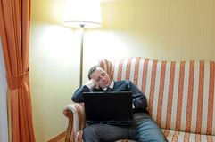 Dreaming man on sofa. A man dreaming on sofa in luxurious modern living room while working at notebook computer royalty free stock images