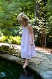 Dreaming of Mermaids. Angelic, blond haired girl explores a garden path. She touches a dark pool of waterr with her toe royalty free stock images