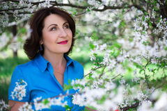 Dreaming middle aged woman in summer garden with blooming cherry. Dreaming middle aged beautiful woman in summer garden with blooming cherry tree royalty free stock photos