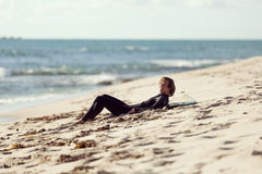 Dreaming of the next big wave. A surfer relaxing and lying on his surfboard at the beach Stock Photography