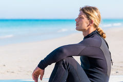 Dreaming of the next big wave. A young surfer with his board on the beach Royalty Free Stock Image